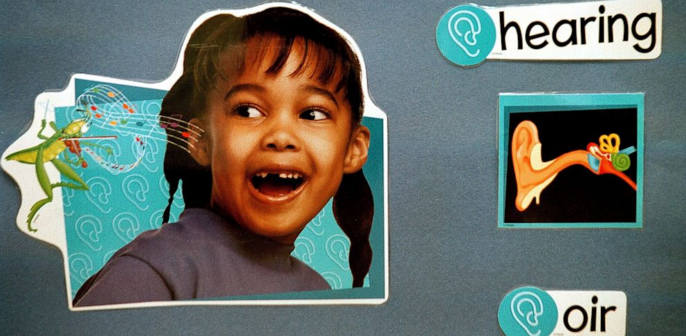"""PHOTO: A bilingual poster on the wall of a first grade classroom translates the Spanish word, """"oir"""" into """"hearing"""" with examples of an ear and a child listening to music at Birdwell Elementary School, September 11, 2003 in Tyler, Texas."""
