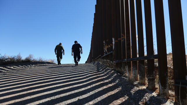 PHOTO:U.S. Customs and Border Protection personnel walk along a section of the recently-constructed fence at the U.S.-Mexico border on February 26, 2013 in Nogales, Arizona.