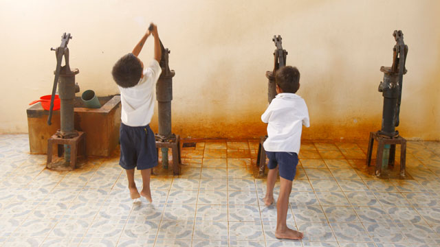 PHOTO: Children pump water at a school in Cambodia in 2010.