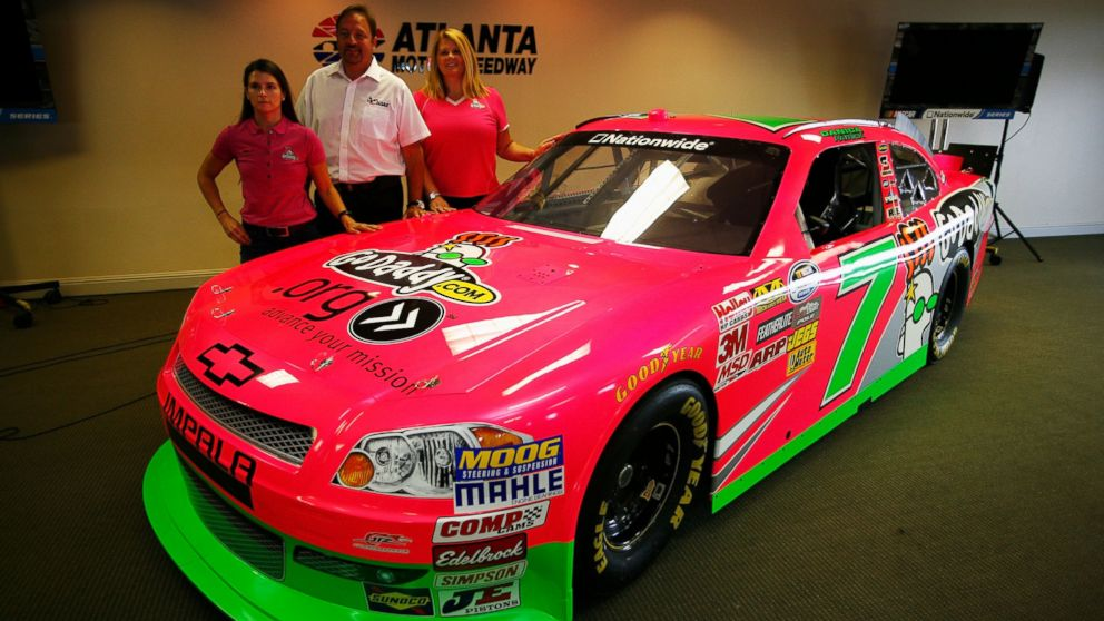 PHOTO: (L-R) Danica Patrick, driver of the #7 GoDaddy.com Chevrolet, Chris Williams from Chase Authentics and Teri DHooge from godaddy.com pose next to the #7 car which has a special paint scheme to raise money for Breast Cancer awareness.