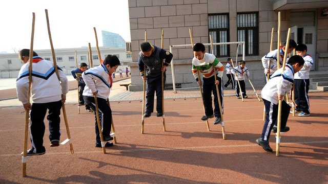 PHOTO:Pupils practice stilt walking during a sports lesson at a primary school in Beijing on January 10, 2011.