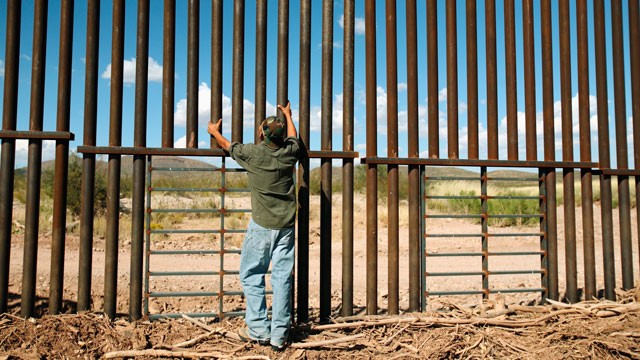 PHOTO:&nbsp;A man stands at a border fence between the United States and Mexico.