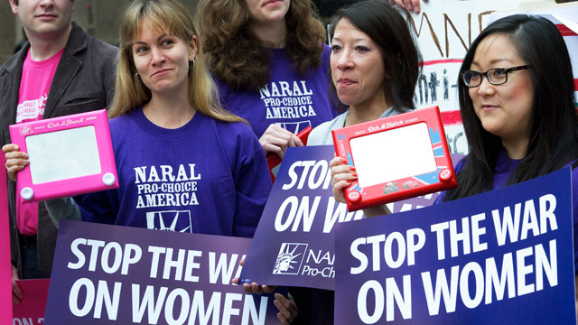 PHOTO: Members of NARAL protest with their 'Etch A Sketch' in hand protest outside a hotel in Washington, D.C., where Republican Presidental hopeful Mitt Romney was holding a political fundraiser on March 22, 2012.