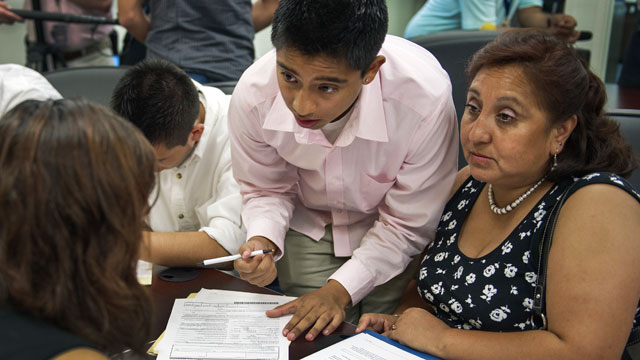 PHOTO: Bolivian Diego Mariaca(C), his mother Ingrid Vaca(R) and brother Gustavo Mariaca(L) fill out deferred action paperwork, August 15, 2012 at the National Immigration Forum in Washington, DC.