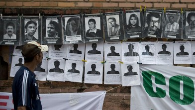 PHOTO: A man looks at portraits of victims during the State-Sponsored Crime Victims International Day in Cali, Colombia.