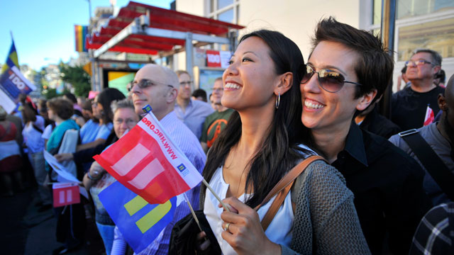 PHOTO: Jenni Chang (L) and Lisa Dazols (R) look on as celebrations ensue in the Castro neighborhood of San Francisco, California, June 26, 2012, after the US Supreme Court struck down The Defense of Marriage Act (DOMA).