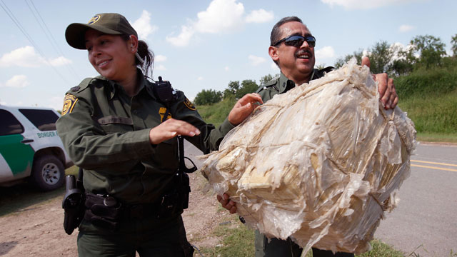 PHOTO: Border Patrol agents carry a bales of marijuana after it was seized from a smuggler near the Mexican border on May 27, 2010 near McAllen, Texas.