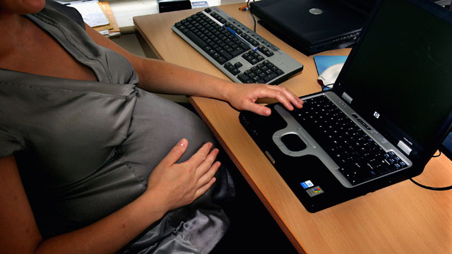 PHOTO: A photo illustration shows a pregnant woman at an office work station.