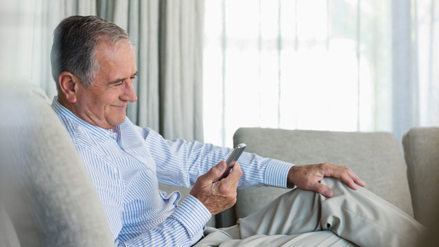 PHOTO:Older man using cell phone on sofa