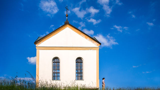 PHOTO:Woman standing beside square chapel against deep blue sky, meadow in foreground.