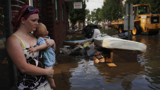 PHOTO: A woman and her baby look out over a flooded street on August 31, 2011 in Wallington, New Jersey. New Jersey was especially hard hit by Hurricane Irene with thousands of residents forced into shelters due to flooded homes.