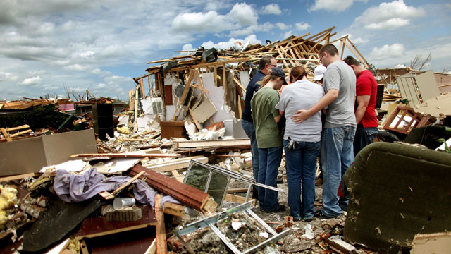 PHOTO: Workers from Skaggs Chiropractic hold a group prayer outside their destroyed office after a massive tornado passed through the town killing at least 123 people on May 25, 2011 in Joplin, Missouri.