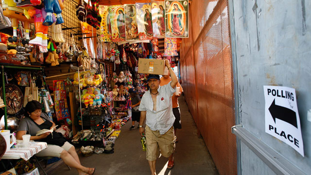 PHOTO: People walk past a directional sign to a polling place inside El Mercado de Los Angeles, a Mexico-style marketplace in the heavily Latino East L.A. area, during the U.S. presidential election on November 6, 2012 in Los Angeles, California.