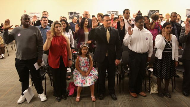 PHOTO: Immigrants take the oath of citizenship at a special Valentine's Day naturalization ceremony for married couples on February 14, 2013 in Tampa, Florida.