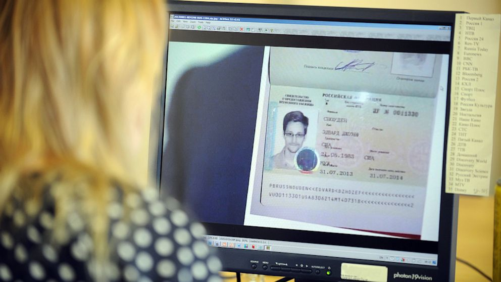 PHOTO: A woman watches a footage on her computer, showing the lawyer of fugitive US intelligence leaker Edward Snowden showing his clients one years asylum permit at Sheremetyevo airport in Moscow.