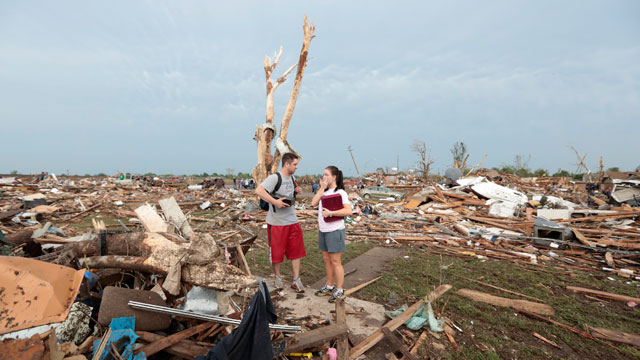 PHOTO:Carlos and Kim Caudillo stand in the debris of their home after a tornado ripped through Moore, Oklahoma on May 20, 2013. The tornado, reported to be at least EF4 strength and two miles wide, touched down on Monday killing at least 51 people.