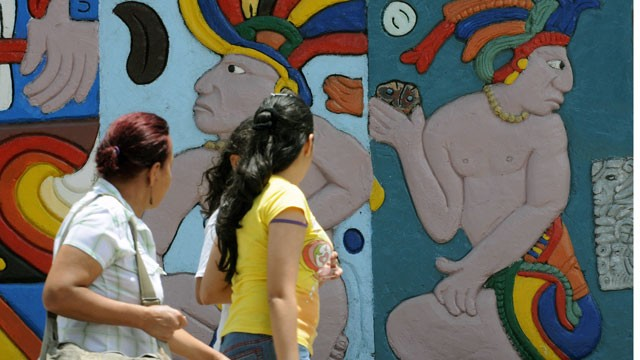 PHOTO: Women walk by a wall displaying Maya figures.