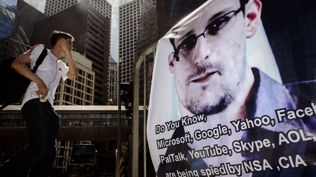 PHOTO: This picture taken on June 18, 2013 shows a man walking past a banner displayed in support of former National Security Agency contractor Edward Snowden in Hong Kong.