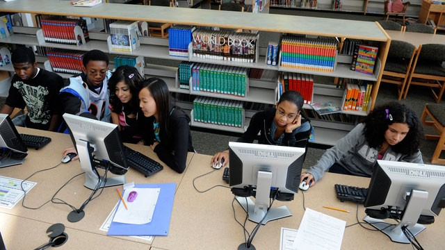 PHOTO: Eight-grade students work on the computers in the library at Denver Pulbic School Bill Roberts.