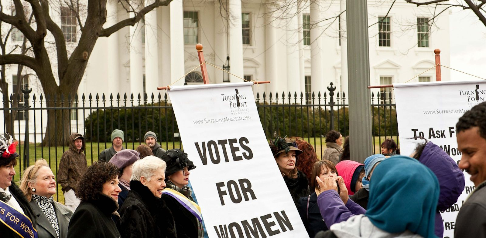 PHOTO: Women hold a sign in front of the White House in Washington on March 2, 2013 during an event to commemorate the 100th anniversary of the Suffrage March.