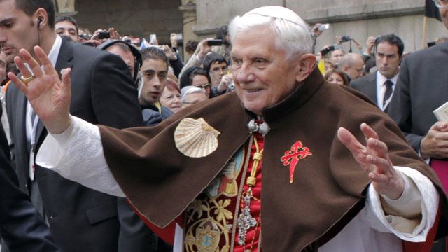 PHOTO: Pope Benedict XVI waves to faithful as he wears a pilgrim cape with a scallop shell and a Santiago cross embroidered on it during his visit in Santiago de Compostela, on November 6, 2010.