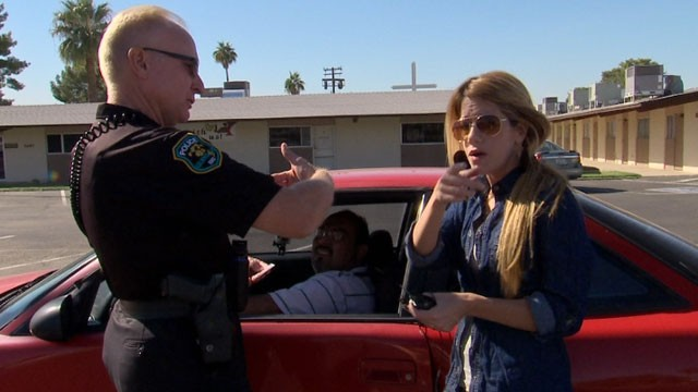 Univision's reporter Andrea Sambuccetti talks to an officer in Phoenix, Arizona, after her producer was pulled over for