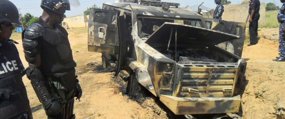 PHOTO: Police look down on a burnt out army personal carrier following an attack by Boko Haram in Damaturu, Nigeria, Oct. 28, 2013.