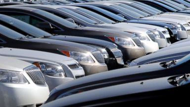 PHOTO: New, unsold automobiles sit in a lot.