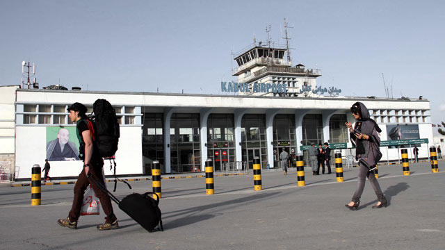 PHOTO: Passengers walk beside a portrait of Afghan President Hamid Karzai at Kabul International Airport, in Kabul, Afghanistan, March 26, 2012.