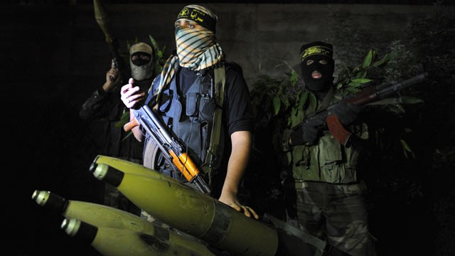 PHOTO: In a picture taken on November 25, 2012, Palestinian militants from the armed wing of the Islamic Jihad organization display rockets at an undisclosed location in the Hamas-run Gaza Strip.
