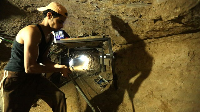 PHOTO: A Palestinian man repairs the entrance of a bombed smuggling tunnel linking the Gaza Strip to Egypt in Rafah, on November 29, 2012.