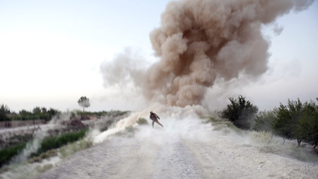 PHOTO: US Marine Sergeant Anthony Zabala runs to safety as an IED explodes in Garmsir district of Helmand Province, Afghanistan.