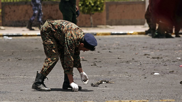 PHOTO: A policeman collects evidence at the site of a suicide bomb attack at a parade squa