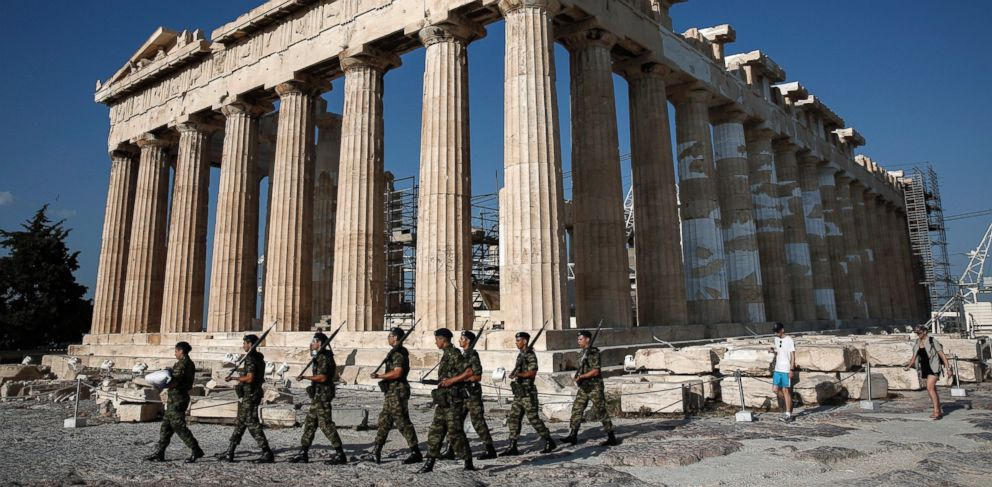 PHOTO: An army contingent carry a Greek flag in front of the Temple of the Parthenon before a hoisting ceremony at the Acropolis Hill in Athens, Greece, June 18, 2015.