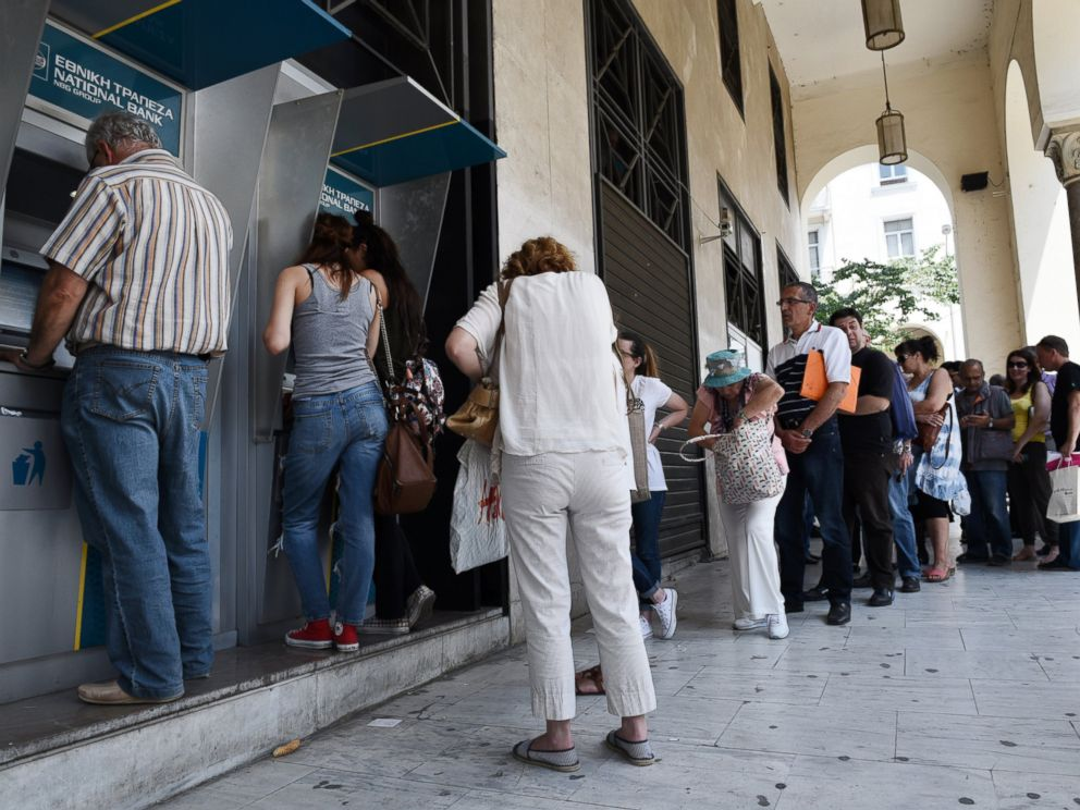 PHOTO: People line up at ATMs outside a National bank branch, June 29, 2015, in the northern Greek port city of Thessaloniki.