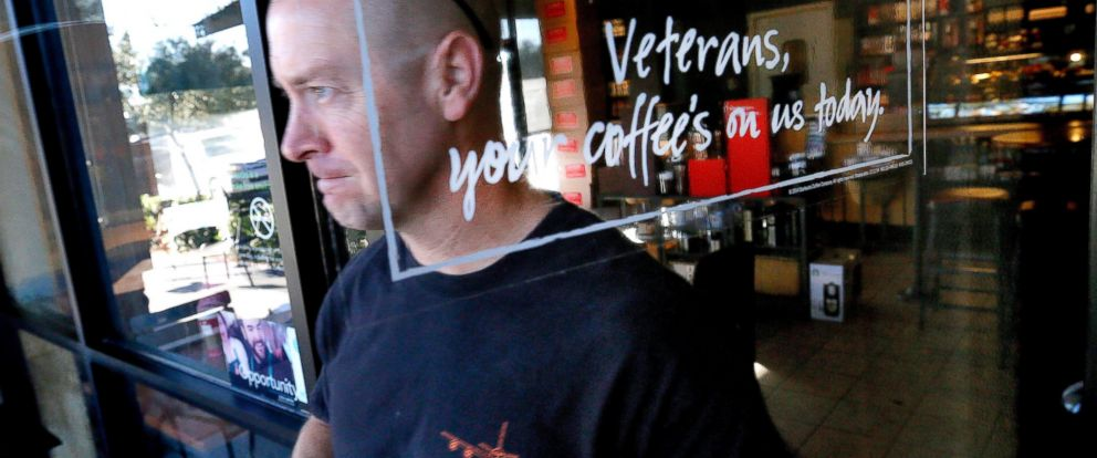 PHOTO: Arizona Air National Guard Lt. Col. Greg Grattop exits a Starbucks with his free coffee, Nov. 11, 2014 in Chandler, Ariz.