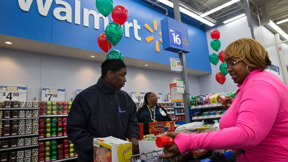 In this Dec. 4, 2013 photo, April Taylor of Upper Marlboro, Md., right, buys items with her son Jarhon Taylor, left, on the opening day of a new Wal-Mart in Washington.