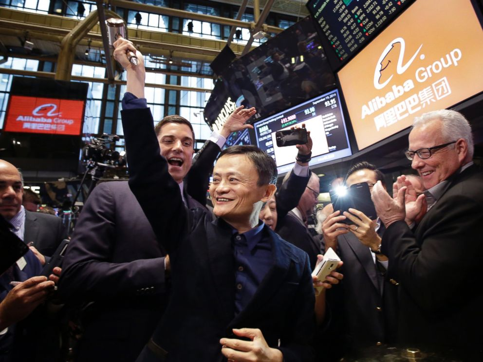 PHOTO: Alibaba founder Jack Ma, center, raises a ceremonial mallet before striking a bell during the companys IPO at the New York Stock Exchange, in New York, Sept. 19, 2014.
