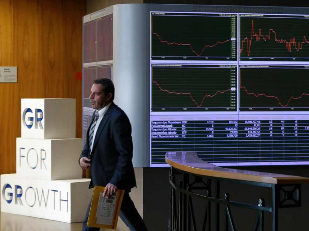 PHOTO: An employee of the Stock Exchange walks next to a display showing stock price movements in Athens, Dec. 29, 2014.