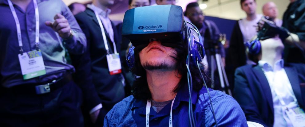 PHOTO: Attendees at the International Consumer Electronics Show play a video game wearing the Oculus Rift virtual reality headset in Las Vegas on Jan. 7, 2014.