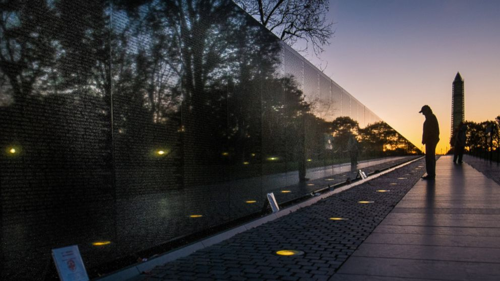 PHOTO: A visitor at the Vietnam War Memorial in Washington passes early in the morning on Veterans Day, Nov. 11, 2013, to look at the names inscribed on the wall.