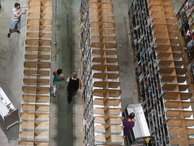 PHOTO: Workers fill inventory among shelves lined with goods at an Amazon warehouse on Sept. 4, 2014 in Brieselang, Germany.