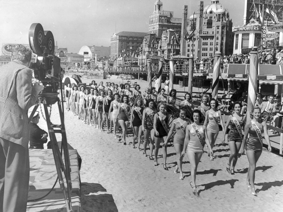 PHOTO: A cameraman films contestants in the Miss America Pageant as they walk on the beach next to the boardwalk at Atlantic City, N.J., Jan. 9, 1939.