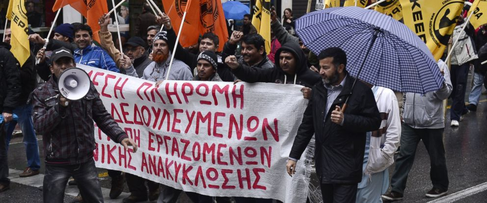 PHOTO: Unpaid migrant workers from recycling companies join a protest march