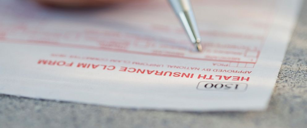 PHOTO: A man filling out a health insurance claim form is pictured in this stock image.