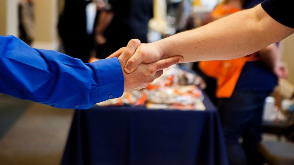PHOTO: A job seeker shakes hands with a representative at the Recruit Military veteran job fair in San Diego, Feb. 27, 2014.