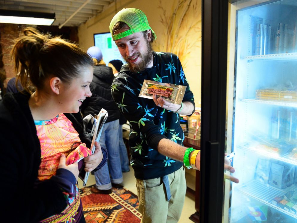 PHOTO: Garrett Sellars shows an edible to Ashly Carius, both of Oklahoma City, at LoDo Wellness. The first day of retail sales of marijuana in Colorado was Jan. 1, 2014.