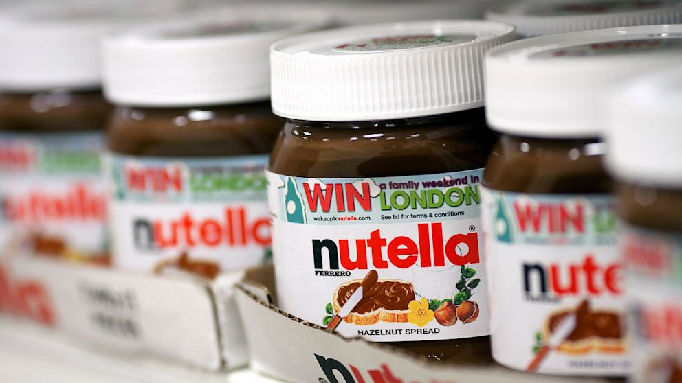 PHOTO: Jars of nutella hazelnut chocolate spread, manufactured by Ferrero S.p.A., sit in boxes on a shelf inside a supermarket.