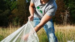 PHOTO: A young man collecting trash is pictured in this stock photo.