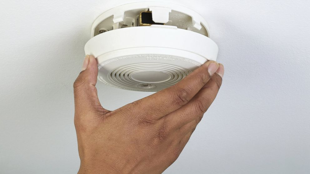 PHOTO: A man installs a smoke detector.